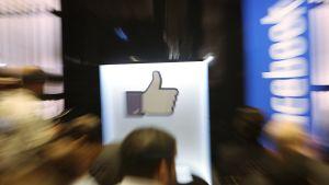 Ihmisiä ja Facebookin peukkulogo.