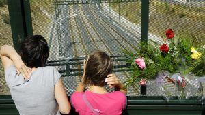 Nuoria tyttöjä junaturman uhrien muistopaikalla radan ylittävällä sillalla Angroisissa lähellä Santiago de Compostelaa 26. heinäkuuta 2013.