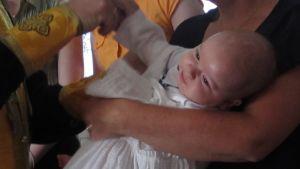 Vauvaa puetaan kastemekkoon kastajaisissa