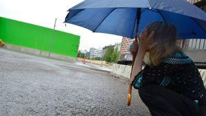 Nuori nainen mököttää sateessa