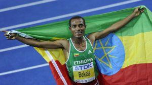 Etiopian Kenenisa Bekele juhlii Etiopian lippuun verhoutuneena Berliinin MM-kilpailuissa.