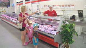 Nainen lapsineen ostoksilla Karelian Lihajalosteen tehtaanmyymälän lihatiskillä.