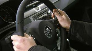 Henkilön kädet ratilla.