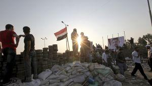 Muslimiveljeskunnan kannattajia barrikadeilla auringon laskun aikaan.