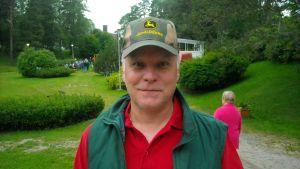 Mies seisoo lippalakissa kesäisen juhlakentän edessä.