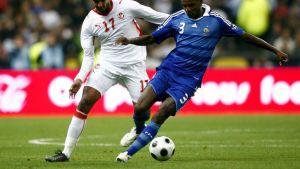 Ranskan Éric Abidal (oik.) suojaa palloa. Vastassa Tunisian Issam Jemaa (vas.).