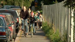 Koululaisia pyöräilemässä kapealla kadulla.