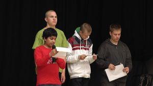 Neljä oppilasta seisoo lavalla ja lukevat koulurauhan julistusta.