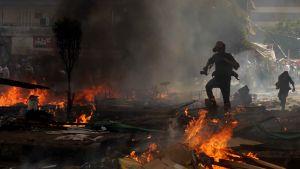 Tunnistamaton valokuvaaja juoksee Kairon kadulla palopesäkkeiden ja kyynelkaasupanosten seassa.