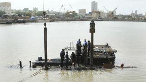Miehiä juuri ja juuri pinnalla olevan sukellusveneen kannella.