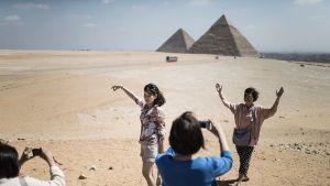 Aasialaisturistit ottavat matkamuistokuvia Gizan pyramideilla.