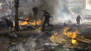 Toimittajat ja kuvaajat juoksevat suojaan syrjäytetyn presidentin Mursin kannattajien ja mellakkapoliisin yhteenottojen aikana.