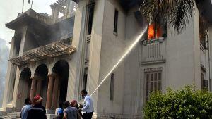 Palomiehet yrittävät sammuttaa syrjäytetyn presidentin Mursin kannattajien ja mellakkapoliisin yhteenottojen aikana palamaan syttynyttä taloa.