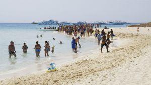 Turisteja hiekkarannalla.