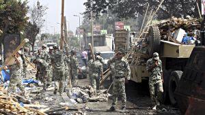 Sotilaat siivoavat romukasoja.