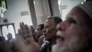 Iäkkäitä miehiä rukoilemassa.