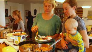 Naiset annostelevat afrikkalaista ruokaa lautaselle.