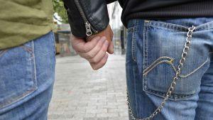 Kaksi henkilöä kävelevät käsi kädessä.