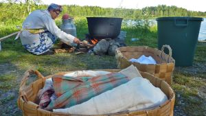 Nainen kohentaa pyykkipadan tulta.