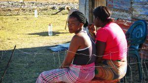Kaksi nuorta naista istuu penkillä ulkona.