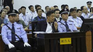 Bo Xilai istuu poliisien välissä.