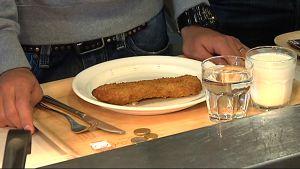 Opiskelijan lautasella yksi kalapihvi