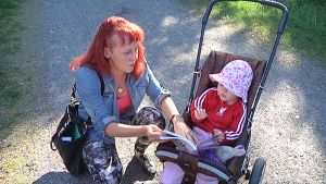 Jasmin näyttää kirjaa rattaissa istuvalle Ilona-tytölle.