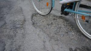 Pyöräilijä ajaa vaurioituneella asvaltilla.