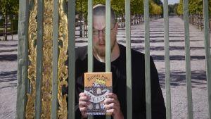 Tuomas Kyrö pitelee uutta kirjaansa käsissään.