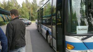 Bussi kuljettaa väkeä Renesasin tiedotustilaisuuteen