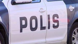 Polis-teksti poliisiauton ovessa.