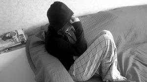 Huppariin pukeutunut nuori istuu sohvalla.