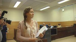 Anneli Auer kävelee oikeussaliin.