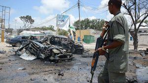 Sotilas kahden tuhoutuneen auton edessä.