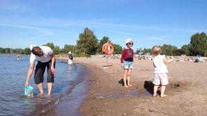 Isä ja lapsia kesäiselllä hiekkarannalla syyskuussa.