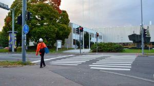 Nainen ylittämässä katua Tampereen yliopiston edessä