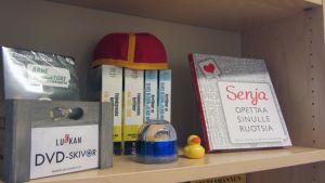 Kuvassa dvd-levyjä, kirja ja vhs-kasetteja ruotsinkielisen tiedotuskeskuksen Luckanin hyllyllä.