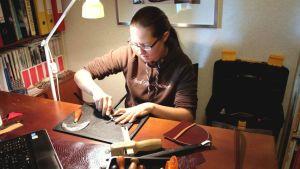 Niina Tolvanen työstää nahkaa monenlaisilla erikoistyökaluilla