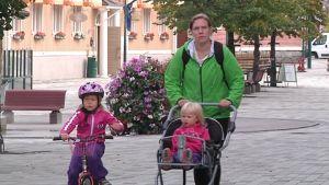 Äiti lasten kanssa kävelykadulla.