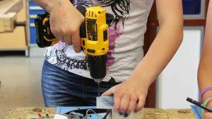 Tyttö poraa eletroniikkapelin muovikanteen reikää.
