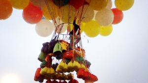 Jonathan Trappe vilkuttaa valtavien ilmapallojen varassa roikkuvan korin kyydissä.