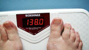Henkilö vaa'alla, jonka lukema on 138 kiloa.