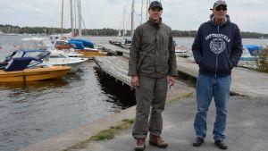 Kuvassa kaksi miestä venerannassa