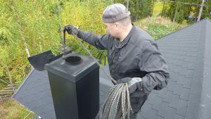 Kainuulainen nuohooja Paavo Oikarinen työnsä äärellä katolla.