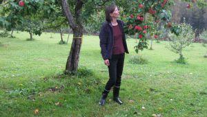Hedelmätarhuri Reetta Lempinen vanhan omenapuun vierellä.