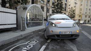 Paikallisten asukkaiden yhteiseen käyttöön tarkoitettu sähköllä toimiva Bluecar lähdössä latausasemalta.