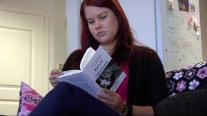 Jenna Miettinen selailee omakustannekirjaansa.