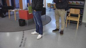 Kaksi ihmistä jonottaa te-palveluita toimistolla