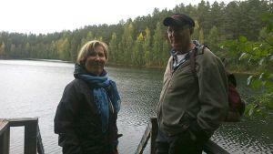 Nainen ja mies seisovat järvenrannalla laiturilla