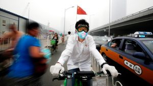 Kiinalainen mies pyöräilee savusumussa pekingissä.